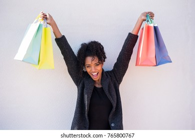 Happy young black woman with shopping bags against a white wall