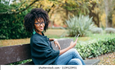 Happy young black woman texting on smartphone in autumn. Stylish girl with afro hair using cell phone outdoor.