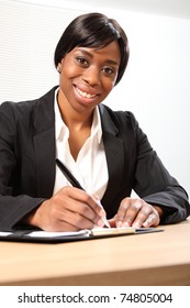 Happy young black woman working in office sitting to her desk signing a document. Picture taken from low angle.