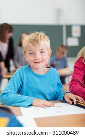 Happy young blond boy pupil at school with a beaming smile sitting at his desk looking at the camera with students and a teacher visible behind