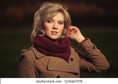 Happy young blond fashion woman wearing classic beige coat and burgundy scarf walking outdoor