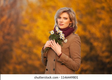 Happy young blond fashion woman wearing classic beige coat with flowers walking outdoor