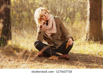 Happy young blond fashion woman sitting on ground in autumn forest Stylish female model wearing classic beige coat and pink scarf