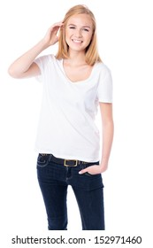 Happy young blond female student in casual jeans standing facing the camera with her hand raised to her hair smiling at the camera, three quarter body on white