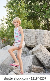 A happy young blond haired girl climbs on a rock pile at a beach park.