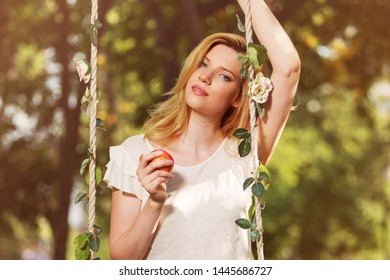 Happy young blond woman with apple in park Stylish fashion model in white t-shirt