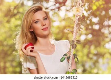 Happy young blond woman with apple in city park Stylish fashion model in white t-shirt