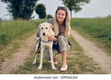 Happy young blond woman crouching down on a rural dirt road with her arms around her dog and a happy smile