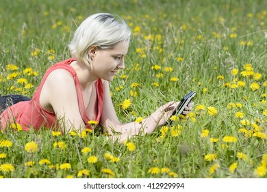 happy young blond woman with digital tablet on flower meadow