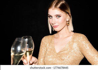 Happy young blond woman in glittering dress clinking flute of champagne with someone and looking at you while enjoying party