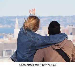Happy young blond woman holding boyfriend and lifting arm to the city of San Francisco, with the Transamerica Pyramid in background