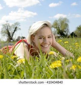 happy young blond woman lying on flower meadow