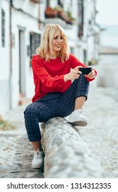 Happy young blond woman sitting on urban background. using smart phone. Smiling blonde girl with red shirt.