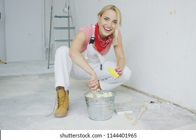 Happy young blond woman in white overalls and work boots sitting on hunkers with small yellow bottle mixing pastel wall paint in bucket at plastered wall and looking at camera.