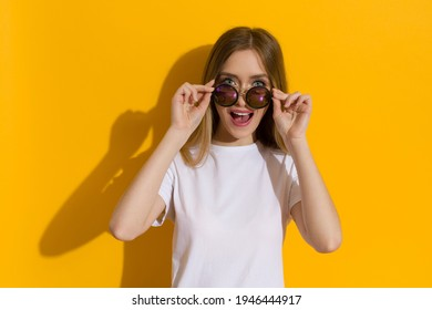 Happy young blond woman in white shirt is looking at camera over sunglasses and talking. Waist up shot on yellow background.