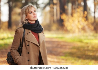 Happy young blonde fashion woman with handbag walking in autumn park Stylish female model wearing classic beige coat and gray scarf