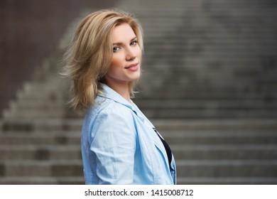 Happy young blonde fashion woman walking on city street Stylish female model in light blue blazer