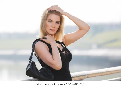 Happy young blonde fashion woman with handbag  Stylish female model in black tank top