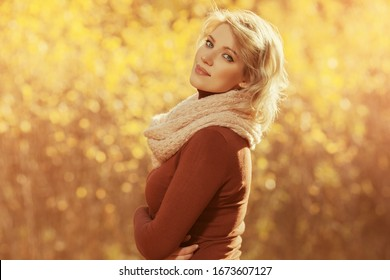 Happy young blonde fashion woman in brown pullover and pink scarf walking outdoor
