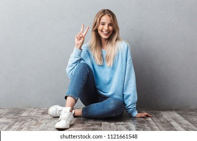 Happy young blonde girl showing peace gesture while sitting on a floor and looking at camera isolated over gray background