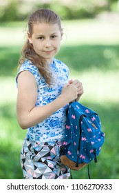 Happy young blonde hair girl standing in park with small backpack in hands, looking at camera