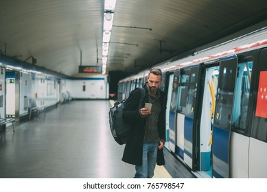 Happy young blonde man with backpacking inside the underground station waiting for the train