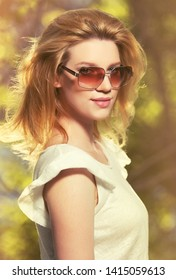 Happy young blonde woman in city park Stylish fashion model in white t-shirt and sunglasses