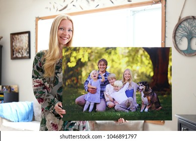 A happy young blonde woman is holding a large wall canvas portrait of her family with young children and a pet dog.