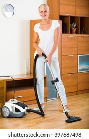 Happy young blonde woman in jeans vacuuming floor at home