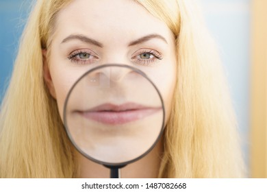Happy young blonde woman showing lips through magnifying glass making it bigger.