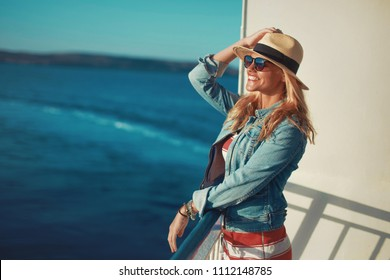 Happy young blonde woman traveler posing on cruise ship deck