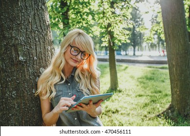 Happy young blonde woman using tablet pc in the park