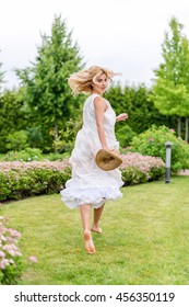 Happy young blonde woman walking barefoot on the green grass. Summer holidays lifestyle concept