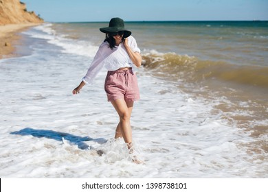 Happy young boho woman walking in sea waves in sunny warm day at tropical island and blue sky. Space for text. Stylish hipster girl in hat  relaxing on beach and smiling. Summer vacation