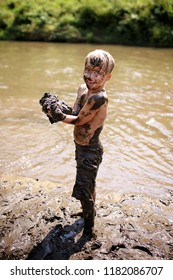 A happy young boy child is covered in mud as he laughs, swims, and plays outside in the river on a summer day.