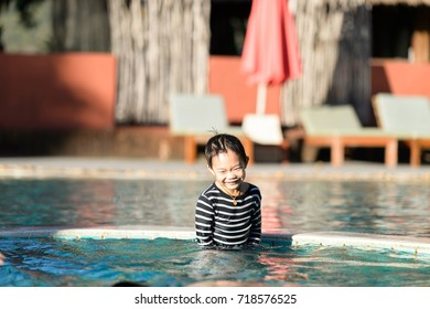 Happy young boy has fun in the swimming pool at noon