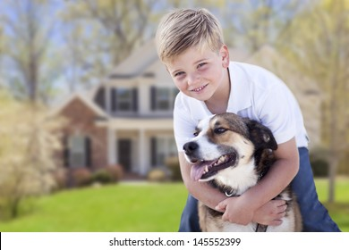 Happy Young Boy and His Dog in Front Yard of Their House.