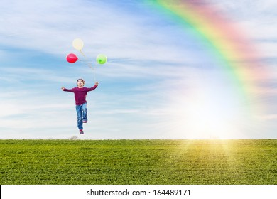 happy young boy levitating with helium balloons against a green meadow and blue sky with a rainbow and a sun burst