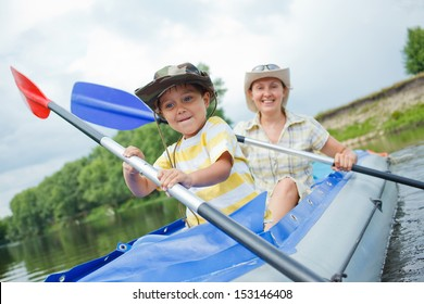 Happy young boy with mother paddling kayak on the river in lovely summer day