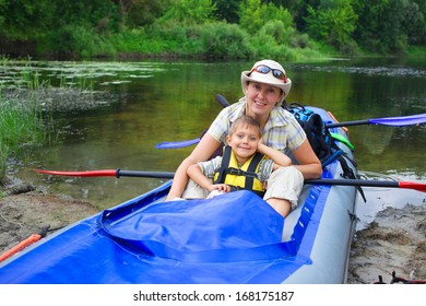 Happy young boy with mother paddling a kayak on the river, enjoying a lovely summer day