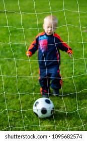 Happy young boy playing in football and scoring the ball in the goal outdoors