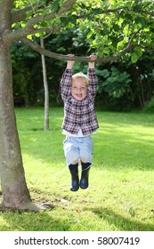 Happy young boy plays in the garden