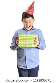 Happy young boy with a red party hat holding a green present box isolated on white background