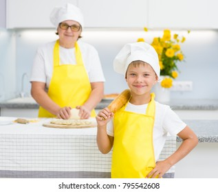 Happy young boy with a rolling pin in the kitchen, grandmom on the background