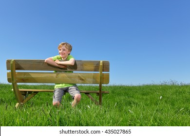 Happy young boy sitting on a bench in summer