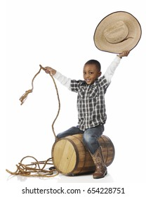 """A happy young boy smiling at the viewer as he """"rides"""" an old barrel as he plays cowboy.  On a white background."""