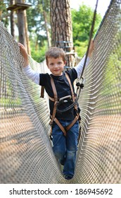 Happy young boy stepping in a stretched mesh in high wire park