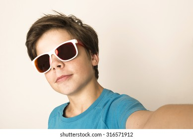 Happy young boy with sunglasses take a selfie with a smartphone at home isolated on white background