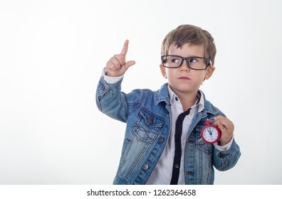 Happy young boy in white t-shirt and jeans jacket thinking and looking up with red clock pointing finger up on white background. Kid with alarm clock