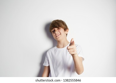 Happy young boy in white T-shirt posing in front of white empty wall. Portrait of fashionable male child. Smiling boy posing, blank wall on background. Concept of children style and fashion